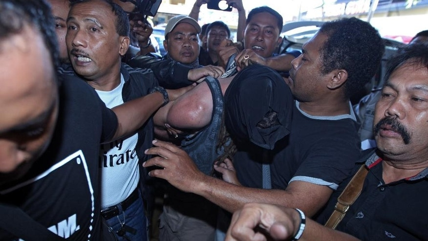 Indonesian police officers escort murder suspect David Taylor, center, as he covers his face at police headquarters in Bali, Indonesia, Friday, Aug. 19, 2016. Indonesian police have arrested an Australian woman and a British man in connection with the alleged murder of a police officer in the tourist resort of Bali. (AP Photo/Firdia Lisnawati)