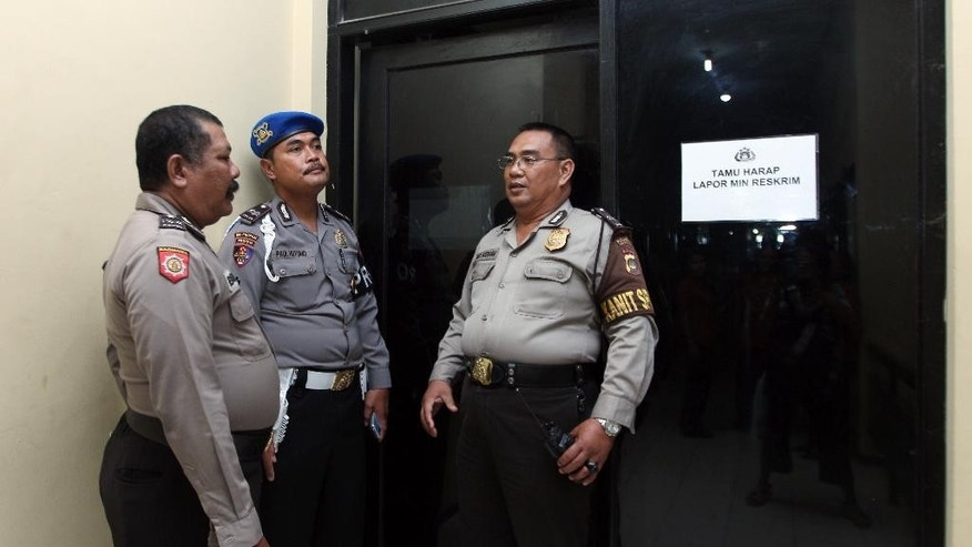 Indonesian police officers guard a door where murder suspect David Taylor is detained at police headquarters in Bali, Indonesia, Friday, Aug. 19, 2016. Indonesian police have arrested an Australian woman and a British man in connection with the alleged murder of a police officer in the tourist resort of Bali.(AP Photo/Firdia Lisnawati)