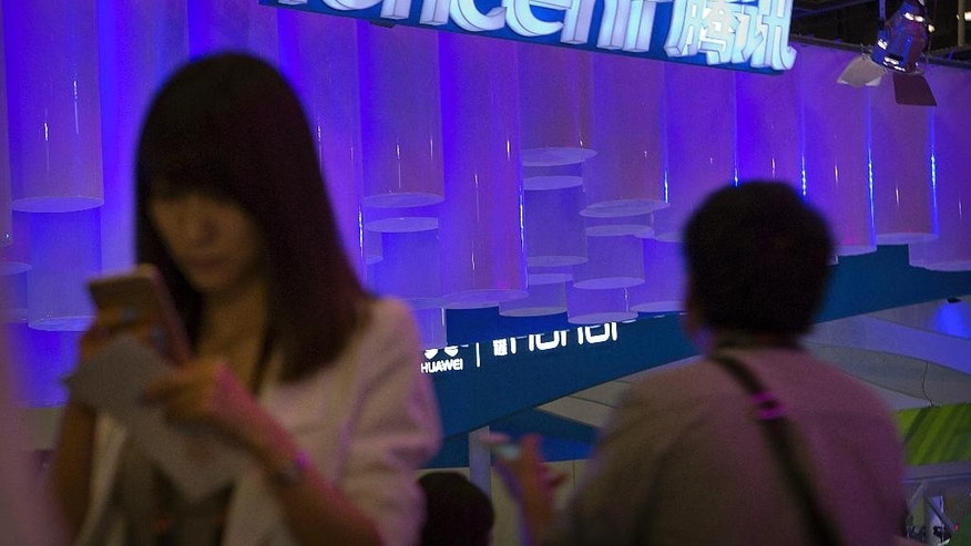 "In this April 29, 2015 photo, a woman uses her smartphone near a booth for the Chinese Internet company Tencent at the Global Mobile Internet Conference in Beijing. Chinese state media reported Thursday, Aug. 18, 2016, that new rules hold chief editors of news websites personally liable for content, months after several portals posted material that was seen as embarrassing to President Xi Jinping. Tencent, one of China's most popular websites, fired its top editor after a July headline mistakenly said Xi delivered a ""furious"" - instead of ""important"" - speech commemorating a Communist Party anniversary. (AP Photo/Mark Schiefelbein)"