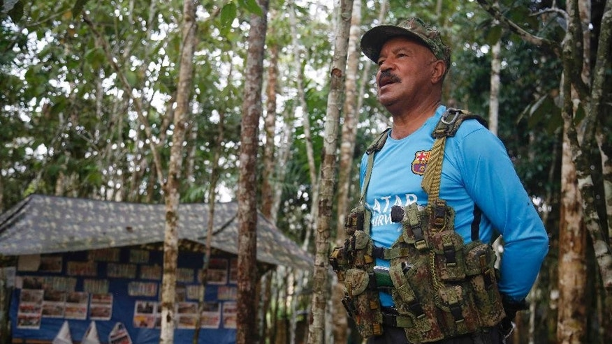 In this Wednesday, Aug. 17, 2016 photo, Martin Corena, acting commander of the Revolutionary Armed Forces of Colombia's southern bloc, FARC, addresses his troops in the southern jungles of Putumayo, Colombia. Corena is calling on President Barack Obama to free a guerrilla leader jailed for more than a decade in the U.S. Corena said Ricardo Palmera's 60-year sentence in connection to the FARC's holding captive of three American defense contracts was incompatible with Obama's support for a peace deal. (AP Photo/Fernando Vergara)