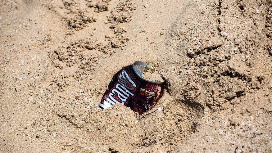 An empty beer can lies on the beach near Havana, Cuba, Thursday, Aug. 18, 2016. At the height of the summer beach season, it's common to see beachgoers spend a day eating, drinking and playing in the water, then leave all their trash in a giant mound on the sand. (AP Photo/Desmond Boylan)