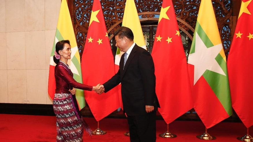 Myanmar's State Counselor Aung San Suu Kyi, left, shakes hands with Chinese President Xi Jinping, right,  pose for the media before their meeting at the Diaoyutai State Guesthouse in Beijing, China, Friday, Aug. 19, 2016.  Suu Kyi was welcomed by Premier Li Keqiang at a formal ceremony Thursday at part of a visit that will include talks with President Xi. The trip ending Sunday is her first to China since her party won a historic majority last year.(Rolex Dela Pena/Pool Photo via AP)