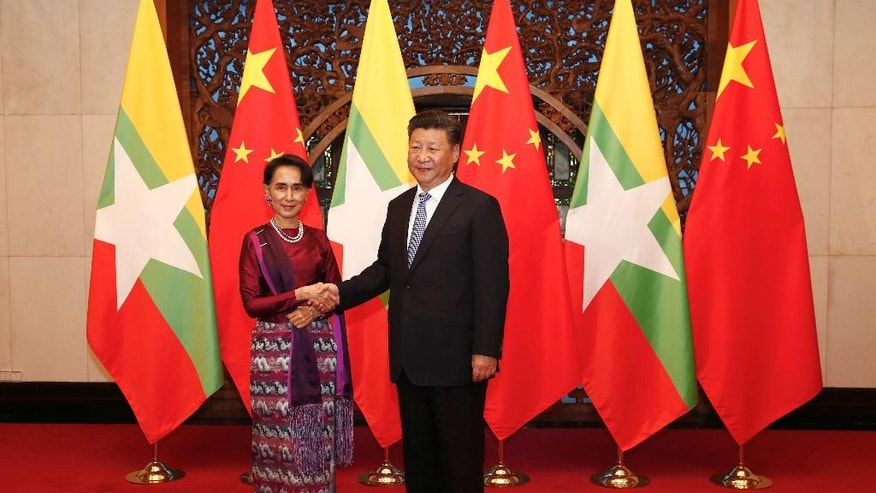 Myanmar's State Counselor Aung San Suu Kyi, left, and Chinese President Xi Jinping, right,  pose for the media before their meeting at the Diaoyutai State Guesthouse in Beijing, China, Friday, Aug. 19, 2016.  Suu Kyi was welcomed by Premier Li Keqiang at a formal ceremony Thursday at part of a visit that will include talks with President Xi. The trip ending Sunday is her first to China since her party won a historic majority last year.(Rolex Dela Pena/Pool Photo via AP)