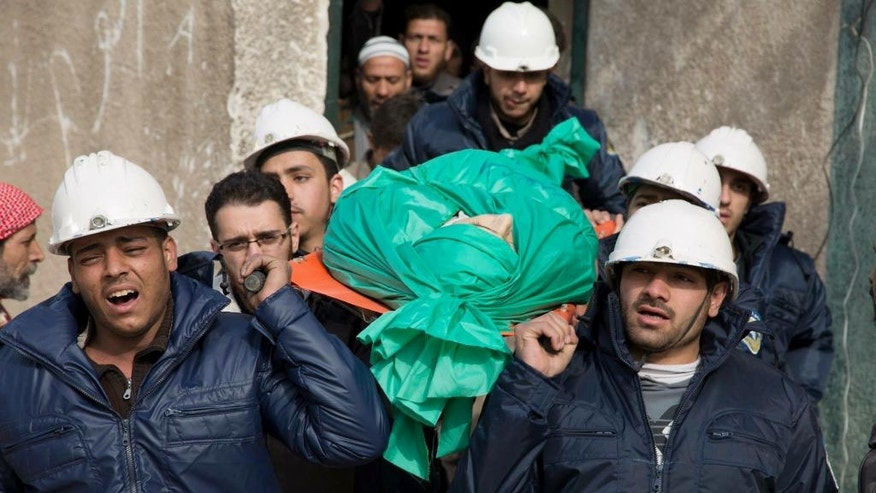 """FILE - In this Wednesday, Sept. 16, 2015 file photo, comrades carry Ilias Mahmoud al-Taweel, a member of Syrian Civil Defence, or White Helmets, during his funeral in in Douma, the suburbs of Damascus. Taweel died while rescuing victims of the shelling of the city. A Syrian volunteer search-and-rescue group has launched a campaign to win its first responders the 2016 Nobel Peace Prize. The Syrian Civil Defense, also known as the White Helmets, operate in the country's war-ravaged opposition areas, where they are exposed daily to bombs dropped by government and Russian warplanes. The group's global following say their task is """"the most dangerous job on the planet."""" (Feras Domy via AP, File) MANDATORY CREDIT"""