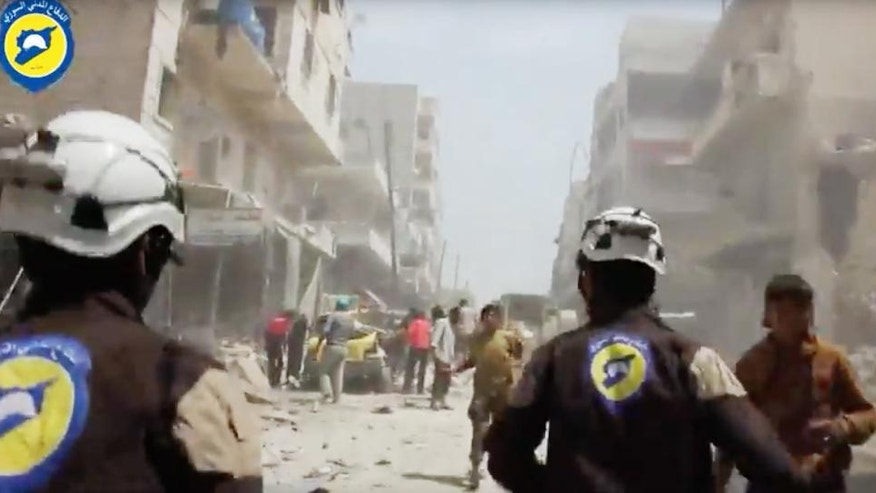 """FILE - In this Sunday, April 24, 2016 file image made from video posted online by the Syrian Civil Defense White Helmets, Civil Defense workers run after airstrikes and shelling hit Aleppo, Syria. A Syrian volunteer search-and-rescue group has launched a campaign to win its first responders the 2016 Nobel Peace Prize. The Syrian Civil Defense, also known as the White Helmets, operate in the country's war-ravaged opposition areas, where they are exposed daily to bombs dropped by government and Russian warplanes. The group's global following say their task is """"the most dangerous job on the planet."""" (Syrian Civil Defense White Helmets via AP video, File)"""