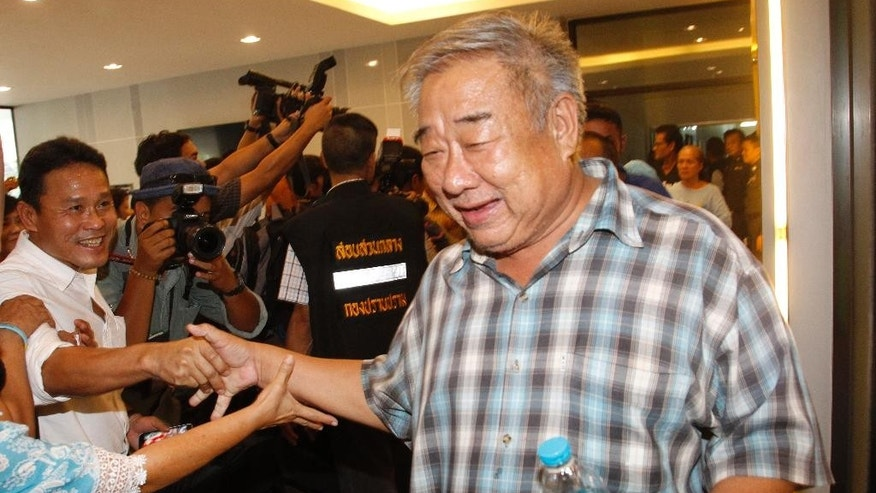 A suspected member of the Revolutionary Front for Democracy Party, right, shakes hands with a relative as he arrives at the Crime Suppression Division in Bangkok, Thailand, Friday, Aug. 19, 2016.  Over a dozen suspects are planned to be charged with running an illegal secret organization which violates the military junta's ban on political gatherings. (AP Photo/Sakchai Lalit)