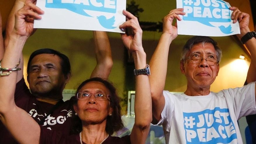 The first batch of communist rebel leaders to be released, from left, Adelberto Silva, Concha Araneta-Bocala and Alan Jasminez, display a hashtag during a news conference following their release on bail Thursday, Aug. 18, 2016, in suburban Quezon city northeast of Manila, Philippines. The communist leadership are seeking the release of more than two dozen rebel leaders whom they claim are members of the negotiating panel as a precondition prior to the Aug. 20-27 peace talks with the Government in Oslo, Norway.(AP Photo/Bullit Marquez)