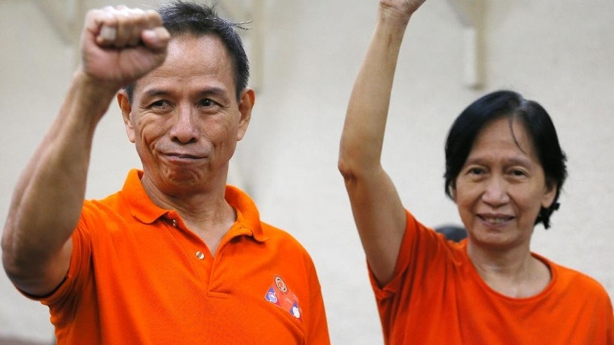 FILE - In this Aug. 11, 2016 file photo, arrested communist rebel leaders Benito, left, and Wilma Tiamzon raise their fists as they await for their bail petition hearing at the Regional Trial Court, Thursday, in Manila, Philippines.   Two top Philippine communist rebel leaders walked out of a maximum security jail Friday, Aug. 19,  to join next week's resumption of Norway-brokered peace talks aimed at ending one of Asia's longest-raging rebellions. (AP Photo/Bullit Marquez, File)