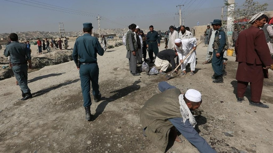 Afghan security police officers inspect the site of bomb blast on the outskirts of Kabul, Afghanistan, Saturday, Aug. 20, 2016. A soldier was killed early Saturday by a sticky bomb placed on his vehicle, Kabul police said. (AP Photo/Rahmat Gul)