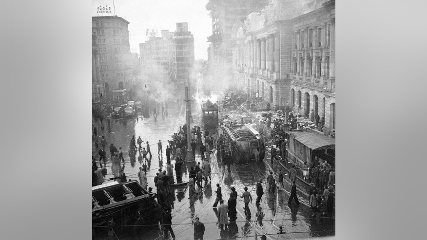 "FILE- This April 1948, file photo shows rioting and looting as a street car is overturned and burned during an uprising following the assassination of Jorge Eliecer Gaitan in Bogota, Columbia. The 1948 assassination of populist firebrand Jorge Eliecer Gaitan sparked the political bloodletting known as ""La Violencia,"" or ""The Violence."" The Revolutionary Armed Forces of Colombia are preparing for a peace deal, in Columbia's half-century guerrilla conflict which has roots in the assassination, which they and the government say could be just weeks away. (AP Photo/E. L. Almen, File)"