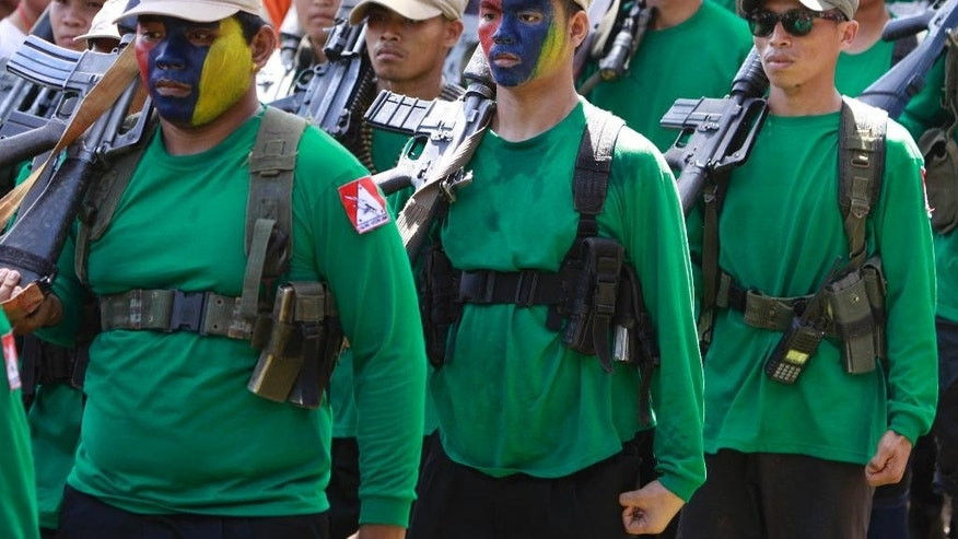 FILE - In this Dec. 26, 2010 file photo, members of the communist New Peoples Army have their faces painted to hide their identity during the celebration of the 42nd anniversary of the Communist Party of the Philippines at Mt. Diwata in southern Philippines. Although less numerous and less violent than Muslim separatist rebels in the country's south, the Maoists have outlived successive Philippine administrations and held out against constant military and police offensives, relying on clandestine cells to pass on orders to members from their exiled leaders. (AP Photo/Pat Roque, File)