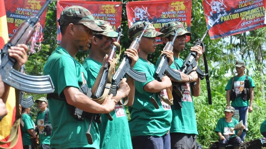 FILE - In this Dec. 26, 2013, file photo communist New People's Army (NPA) rebels hold weapons in formation in the hinterlands of Davao, Southern Philippines. Although less numerous and less violent than Muslim separatist rebels in the country's south, the Maoists have outlived successive Philippine administrations and held out against constant military and police offensives, relying on clandestine cells to pass on orders to members from their exiled leaders. (AP Photo, File)