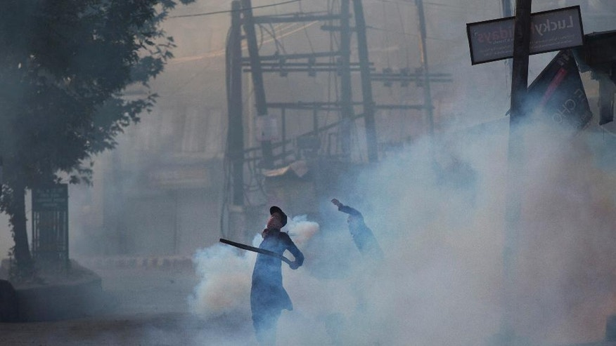 Kashmiri Muslim protesters throw rocks and exploded tear gas shell at Indian paramilitary soldiers in Srinagar, Indian controlled Kashmir, Friday, Aug. 19, 2016. The Himalayan region has been under curfew for almost six weeks as the largest street protests in years erupted after Indian troops killed a top rebel leader. (AP Photo/Dar Yasin)