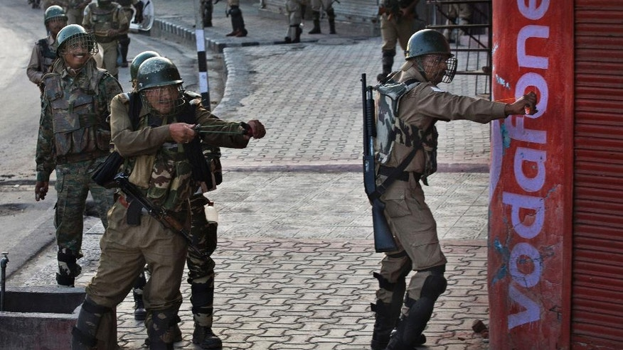 Indian paramilitary soldiers use sling shots to target Kashmiri Muslim protesters in Srinagar, Indian controlled Kashmir, Friday, Aug. 19, 2016. The Himalayan region has been under curfew for almost six weeks as the largest street protests in years erupted after Indian troops killed a top rebel leader. (AP Photo/Dar Yasin)