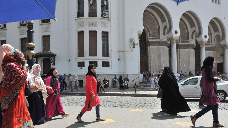 A veiled woman walks in central Algiers, Wednesday Aug. 10, 2016. Mosques are going up, women are covering up and bars, restaurants and shops selling alcoholic beverages are shutting down in a changing Algeria where, slowly but surely, Muslim fundamentalists are gaining ground. (AP Photo/Ouahab Hebbat)