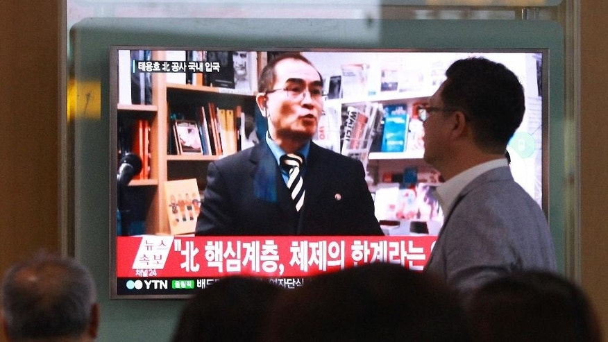 "FILE - In this Wednesday, Aug. 17, 2016 file photo, people watch a TV news program showing a file image of Thae Yong Ho, a minister at the North Korean Embassy in London, at Seoul Railway Station in Seoul, South Korea. North Korea on Saturday, Aug. 20, 2016, said Thae, a senior North Korean diplomat who recently defected to South Korea, is a criminal and ""human scum,"" in its first official response to the defection. The letters read ""A high-ranking North Korean diplomat."" (AP Photo/Ahn Young-joon. File)"