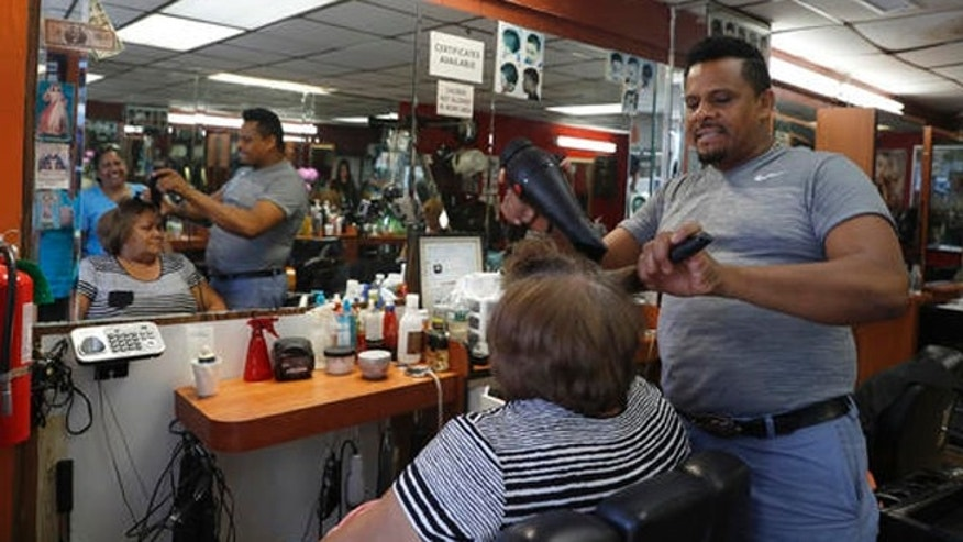 In this Wednesday, Aug. 17, 2016, photo Manolo Reyes works on a clients hair while speaking during an interview with The Associated Press in his hair salon in the Ozone Park neighborhood of the Queens borough of New York.  The shooting of an imam and his assistant near their New York mosque has unnerved Muslim residents of the Ozone Park section of Queens.   (AP Photo/Mary Altaffer)