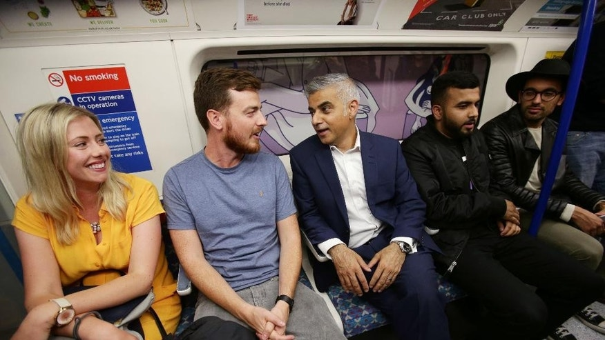 Mayor of London Sadiq Khan, center, chats with passengers as he travels on a northbound Victoria line tube train during the launch of London's Night Tube Saturday, Aug. 20, 2016. The London Underground introduced limited overnight service Saturday, a move city leaders hope will make the British capital a truly 24-hour city and bolster the local economy. (Yui Mok/PA via AP)