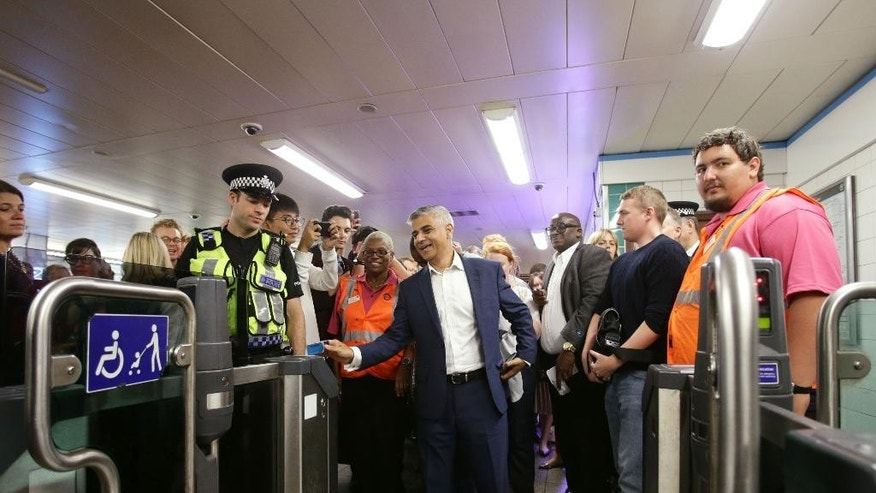 Mayor of London Sadiq Khan, center,  touches his Oyster card at an entry gate at Brixton Underground Station during the launch of London's Night Tube Saturday, Aug. 20, 2016. The London Underground introduced limited overnight service Saturday, a move city leaders hope will make the British capital a truly 24-hour city and bolster the local economy. (Yui Mok/PA via AP)