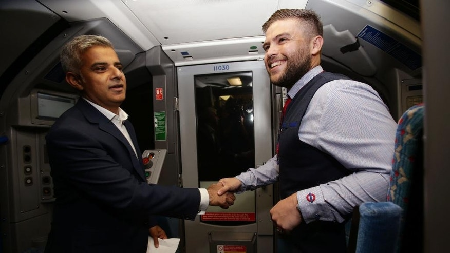 Mayor of London Sadiq Khan, left, shakes hands with Daniel George, a driver of the first Night Tube, in the driver's carriage of a Victoria line tube train at Brixton Underground Station during the launch of London's Night Tube Saturday, Aug. 20, 2016. The London Underground introduced limited overnight service Saturday, a move city leaders hope will make the British capital a truly 24-hour city and bolster the local economy. (Yui Mok/PA via AP)