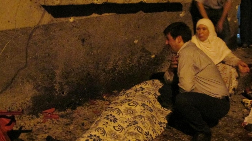 A man cries over a covered body after an explosion in Gaziantep, southeastern Turkey, late Saturday, Aug. 20, 2016. Gaziantep Province Gov. Ali Yerlikaya said the deadly blast, during a wedding near the border with Syria, was a terror attack. (IHA via AP)