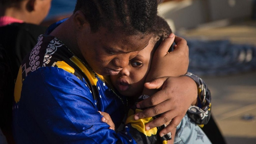 A woman from Nigeria comforts a child on the Astral vessel after been rescued by members of Proactiva Open Arms NGO, during a rescue operation at the Mediterranean sea, about 17 miles north of Sabratah, Libya, Saturday, Aug. 20, 2016. Migrants seemingly prefer to face the dangers of the journey towards Europe, rather than stay at home. (AP Photo/Emilio Morenatti)