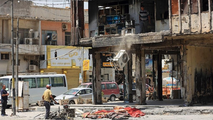 People clear debris from their damaged apartment at the site of a deadly Islamic State group-claimed mall bombing in the Karradah neighborhood of Baghdad, Iraq, Sunday, Aug. 21, 2016. Traffic began to file through the busy Karradah street Sunday for the first time in nearly two months. The scene of the blast that ultimately claimed the lives of nearly 300 people, according to the ministry of health, sat as a memorial to the dead for weeks after the attack. The July 3 attack was the single deadliest bombing in Baghdad since the 2003 toppling of Saddam Hussein and it fueled anger toward the Iraqi government over the lack of security in the capital. (AP Photo/ Khalid Mohammed)