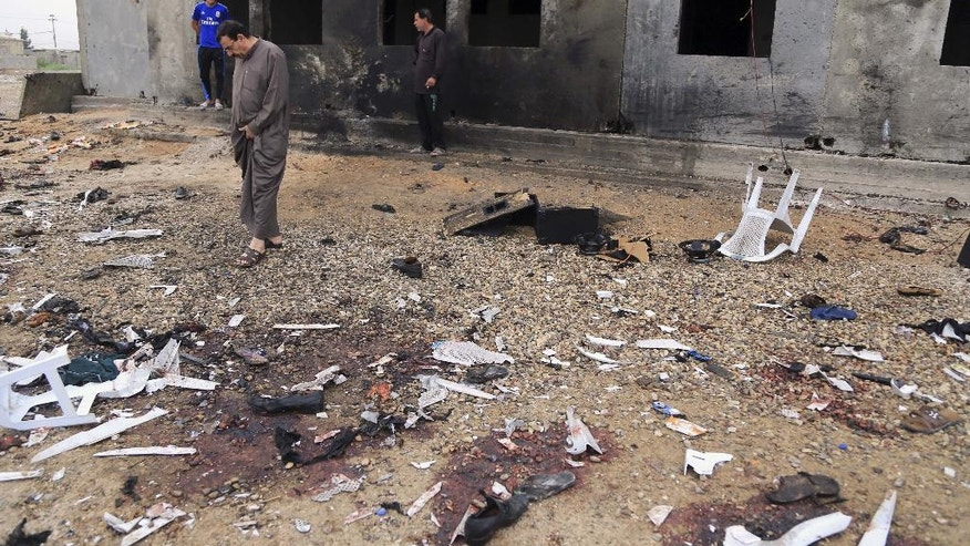 FILE - In this March 26, 2016, file photo, people inspect the aftermath of a suicide bombing that killed 29 and wounded 60 at a soccer field in Iskandariya, 25 miles (about 40 kilometers) south of Baghdad, Iraq. The Islamic State group claimed responsibility and released a photo of the attacker where he appears to be no more than 16 years old. The suicide attacker who detonated his explosives amid an outdoor Kurdish wedding party, Saturday, Aug. 20, 2016, in southeastern Turkey, killing at least 51 people, was an Islamic State group child as young as 12 years old. (AP Photo/Karim Kadim, File)