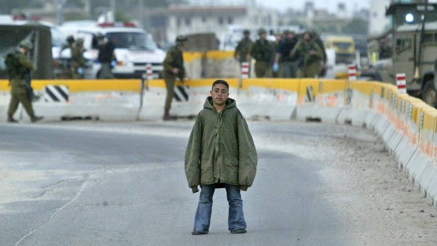 FILE -- In this March 24, 2004 file photo, Palestinian youth Hussam Abdo, a would-be suicide bomber, stares at journalists as Israeli soldiers present him to the media, following his arrest at the Hawara checkpoint near the northern West Bank city of Nablus. Sappers later detonated the bomb under the jacket. The suicide attacker who detonated his explosives amid an outdoor Kurdish wedding party, Saturday, Aug. 20, 2016, in southeastern Turkey, killing at least 51 people, was an Islamic State group child as young as 12 years old. (AP Photo/Lefteris Pitarakis, File)