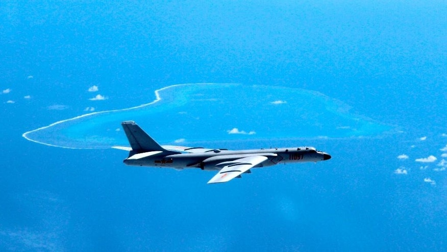 FILE - In this undated file photo released by Xinhua News Agency, a Chinese H-6K bomber patrols the islands and reefs in the South China Sea. Chinese planes and ships held war games in the Sea of Japan last week, the military said in a statement on its website late Saturday, Aug. 20, 2016, during which Beijing displayed its latest-generation frigate Jingzhou and destroyer Xi'an at a time of bitter territorial disputes with Asian neighbors. The ministry said aircraft were guided to their targets with the aid of early warning planes. Other types of aircraft involved weren't identified, although China has been touting the capabilities of its latest-generation long-range H-6K strategic bomber equipped with the DH-20 land-attack cruise missile, giving it the ability to hit targets as far away as Australia. (Liu Rui/Xinhua via AP, File)