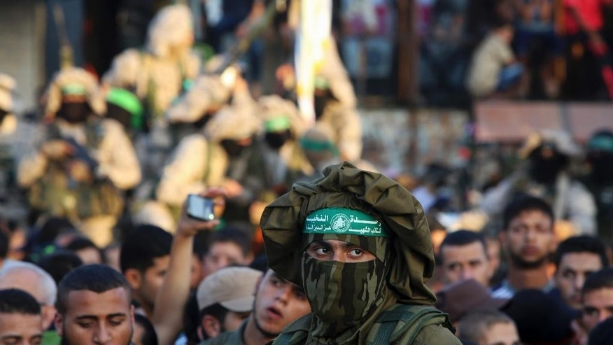 "A Palestinian masked member from the Izzedine al-Qassam Brigades, a military wing of Hamas, stands guard during a rally in Rafah refugee camp, Gaza Strip, Sunday, Aug. 21, 2016. The Arabic on headband reads, ""no God but Allah and Muhammad is his messenger. Izzedine al-Qassam Brigades"". (AP Photo/Adel Hana)"