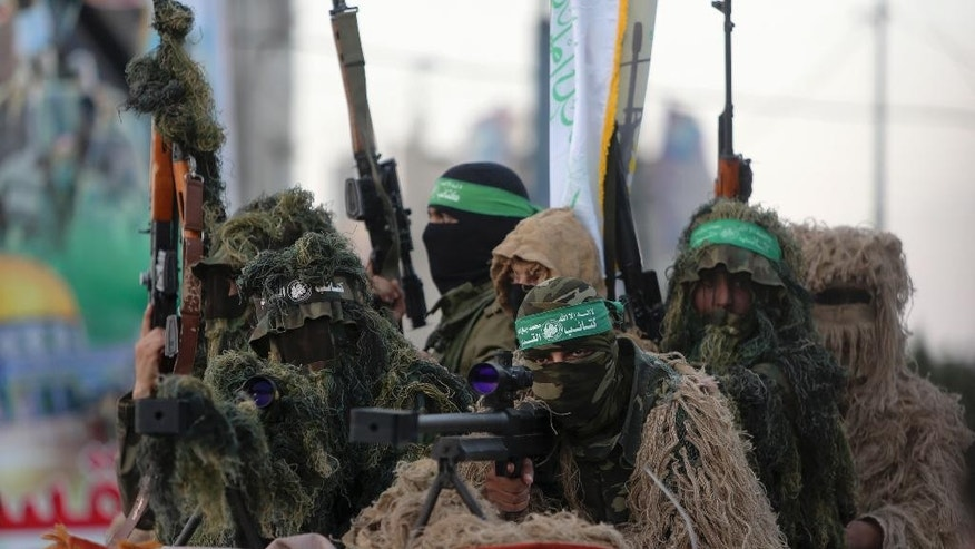 "Palestinian masked members from the Izzedine al-Qassam Brigades, a military wing of Hamas, wear camouflage while sitting behind a sniper gun during a rally along the streets of Rafah refugee camp, Gaza Strip, Sunday, Aug. 21, 2016. The Arabic on their headbands reads, ""no God but Allah and Muhammad is his messenger. Izzedine al-Qassam Brigades"". (AP Photo/Adel Hana)"