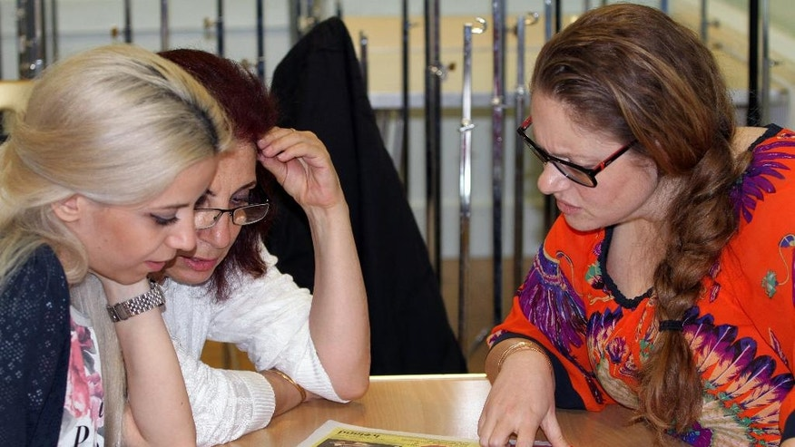 In this photo taken on Thursday, July 28, 2016, two Syrian refugees, left, concentrate during an English lesson with a volunteer teacher in London. As the U.K. struggles to implement its commitment to resettle more than 20,000 Syrians, the government is counting on charities and community groups to help the newcomers adjust to life in Britain. The Home Office has for the first time set up a program to allow local organizations to sponsor refugees and the agency's website directs volunteers to migrant charities that need their help.  (AP Photo/Adela Suliman)