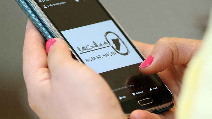 In this photo taken on Thursday July 28, 2016, Fardous Bahbouh, a Syrian refugee, scrolls through her mobile phone showing the message 'Ahlan Wa Sahlan', 'Welcome' in Arabic, the homescreen of the online group created to bring together Syrian refugees newly arrived in Britain, in London.  As the U.K. struggles to implement its commitment to resettle more than 20,000 Syrians, the government is counting on charities and community groups to help the newcomers adjust to life in Britain. (AP Photo/Adela Suliman)
