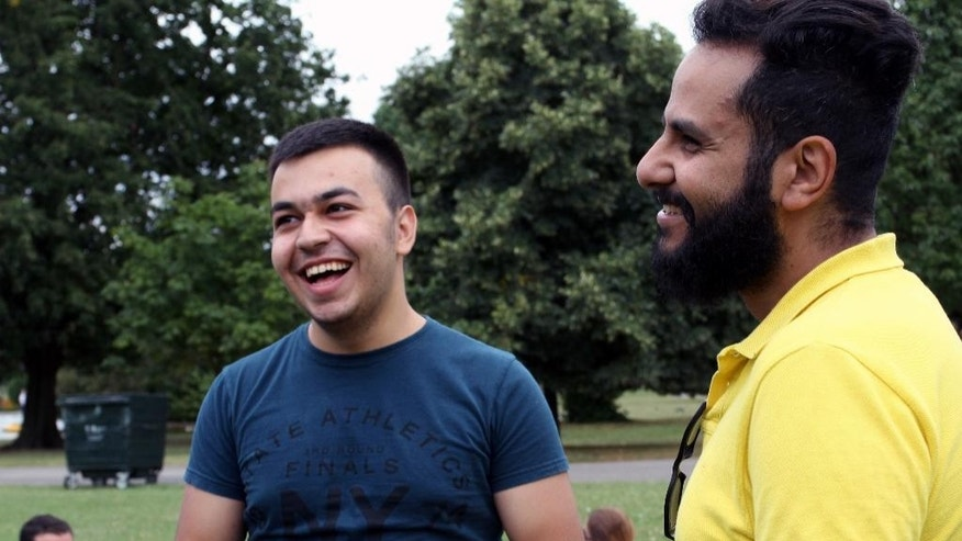 In this photo taken on Saturday, July 30, 2016, Karam AlHabbal, a Syrian refugee, left, laughs with a volunteer at a picnic in Regent's Park, London, after gaining residency status but will reveal few details of his journey to Britain for fear of endangering others.  Karam AlHabbal, who dreams of going to a British university and becoming a pilot, he is confident and his English is already so good that he volunteers to help others.  As the U.K. struggles to implement its commitment to resettle more than 20,000 Syrians, the government is counting on charities and community groups to help the newcomers adjust to life in Britain. (AP Photo/Adela Suliman)