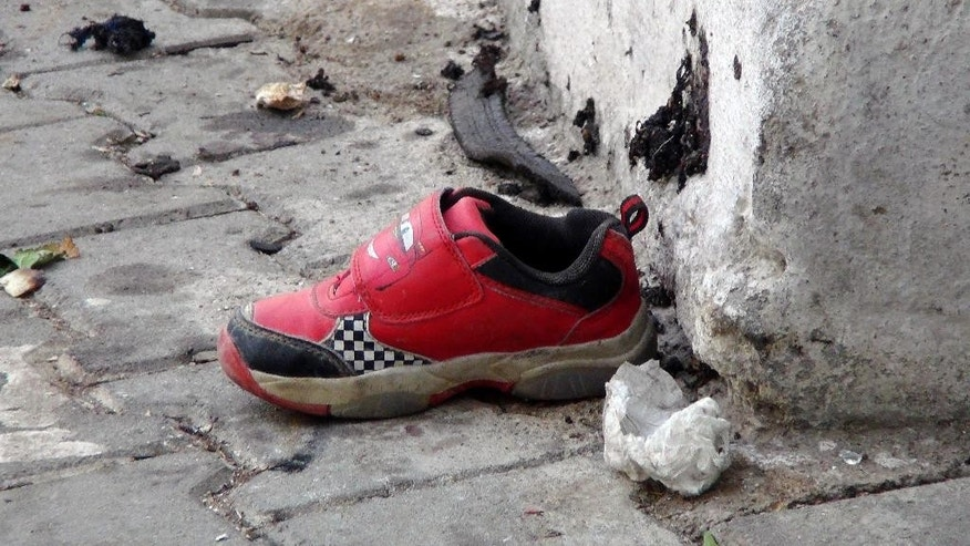 "The shoe of a young victim and a piece of metal lay near the scene just hours after Saturday's bomb attack in Gaziantep, southeastern Turkey, early Sunday, Aug. 21, 2016, targeting an outdoor wedding party in southeastern Turkey killing dozens of people and wounding dozens more. Deputy Prime Minister Mehmet Simsek said the ""barbaric"" attack in Gaziantep, near the border with Syria, on Saturday appeared to be a suicide bombing. Turkish authorities have put a temporary ban on distribution of images relating to Saturday's Gaziantep attack within Turkey. (IHA via AP)"