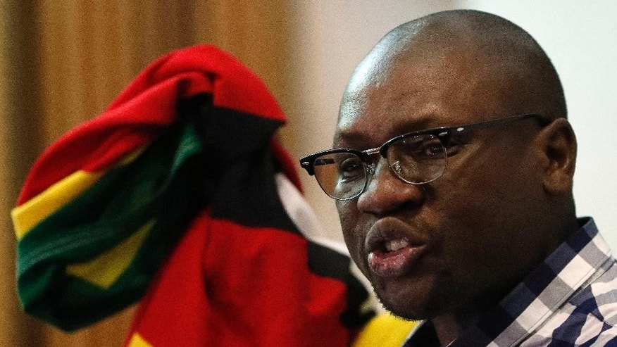 FILE -- In this July 28, 2016 file photo Zimbabwean pastor Evan Mawarire, holds his country's flag whilst singing the national anthem before addressing his supporters at the University of the Witwatersrand in Johannesburg, South Africa. Mawarire, a popular pastor who galvanized thousands of Zimbabweans into anti-government protests has become a subject of derision, fighting accusations of being a coward after he left neighboring South Africa citing safety concerns before going to the United States. (AP Photo/Themba Hadebe, File)