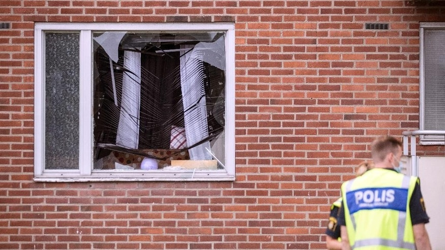 Police forensic officers investigate the area after an explosion at an apartment block, in Biskopsgarden, Goteborg, south of Sweden, Monday, Aug. 22, 2016. Swedish police say that an 8-year-old boy was killed in a hand grenade attack at an apartment in the southwestern city of Goteborg early Monday. (Bjorn Larsson Rosvall/TT News Agency via AP)