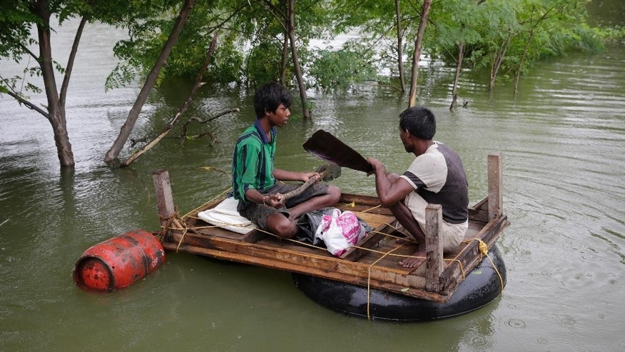 Two men carry essentials like a gas cylinder to their temporary shelter by a makeshift raft after several areas were flooded in Allahabad, India, Monday, Aug. 22, 2016. Heavy rainfall in the upper reaches of the country has caused rivers to overflow endangering lives and properties of people along the river Ganges as also in other parts of the country. (AP Photo/Rajesh Kumar Singh)