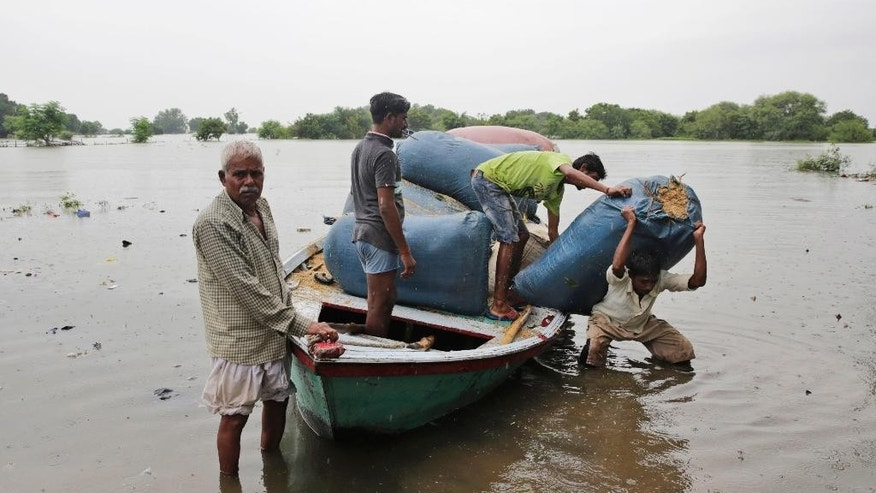 People bring in fodder for their livestock by boat as several areas get flooded in Allahabad, India, Monday, Aug. 22, 2016. Heavy rainfall in the upper reaches of the country has caused rivers to overflow endangering lives and properties of people along the River Ganges as also in other parts of the country. (AP Photo/Rajesh Kumar Singh)