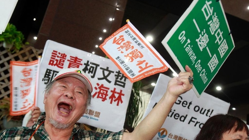A protester shouts and waves placards written with a slogan reading ''One Taiwan, One China'' outside the venue of a dinner party held by Taipei Mayor Ke Wen-je for Sha Hailin, head of the United Front Work Department of Chinese Communist Party's Shanghai Municipal Committee, on the eve of Taipei-Shanghai forum in Taipei, Taiwan, Monday, Aug. 22, 2016. The Chinese envoy arrived in Taiwan on Monday for a city-to-city dialogue, amid a chill in relations between the sides following the inauguration of the island's independence-leaning president, Tsai ing-wen, in June. (AP Photo/ Chiang Ying-ying)