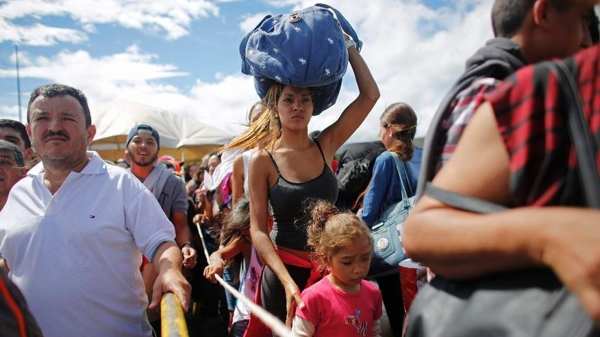 FILE - In this July 17, 2016 file photo, a woman carrying a bundle on her head waits in line to cross the border into Colombia in San Antonio del Tachira, Venezuela. Colombia will deport Venezuelans in the country illegally amid warnings that the recent reopening of the two nations' border could be fueling a wave of illegal immigration. Migration officials said Monday, Aug. 22, 2016, 33 Venezuelan women were detained in the northern city of Barrancabermeja and would be taken to the border for expulsion soon. (AP Photo/Ariana Cubillos, File)