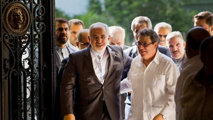 Iranian Foreign Minister Mohammad Javad Zarif, left, is welcomed by Cuban Foreign Minister Bruno Rodriguez, in Havana, Cuba, Monday, Aug. 22, 2016. Iran's foreign minister begun a Latin American tour in Cuba, declaring Iran and Cuba united by their histories of resisting what he called U.S. atrocities. Zarif also plans to visit Nicaragua, Ecuador, Chile, Bolivia and Venezuela. (AP Photo/Ramon Espinosa)