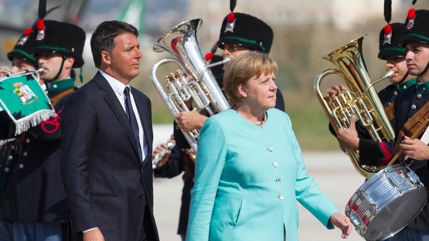 Italian Premier Matteo Renzi, left, and German Chancellor Angela Merkel review the honor guard at Naples' Capodichino international airport, Monday, Aug. 22, 2016. The leaders of Italy, France and Germany headed Monday to one of the birthplaces of European unity in a symbolic bid to relaunch the European project following Britain's decision to leave the EU. (AP Photo/Riccardo De Luca)