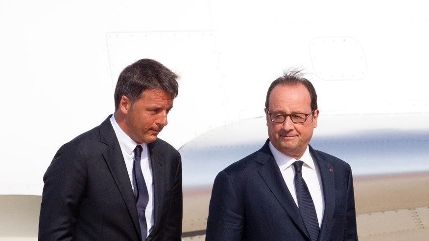 Italian Premier Matteo Renzi, left, welcomes French President Francois Hollande at Naples' Capodichino international airport, Monday, Aug. 22, 2016. The leaders of Italy, France and Germany headed Monday to one of the birthplaces of European unity in a symbolic bid to relaunch the European project following Britain's decision to leave the EU. (AP Photo/Riccardo De Luca)