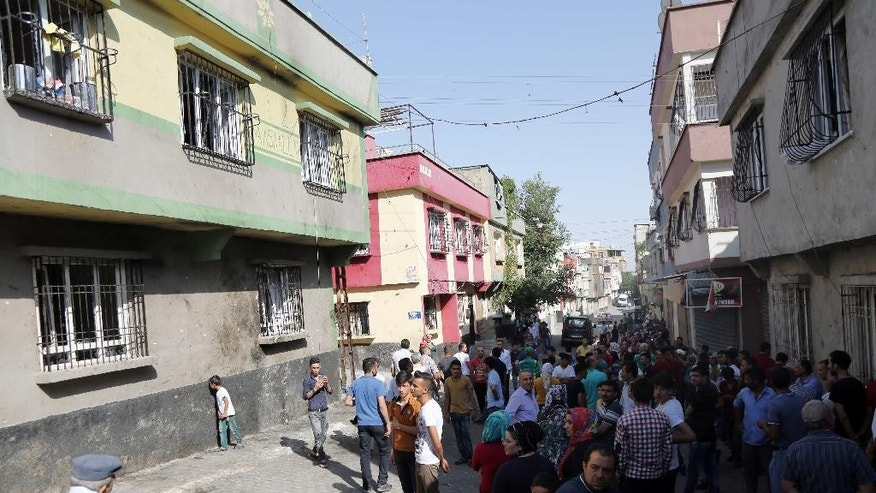 "People gather near to the scene of Saturday's bomb attack targeting an outdoor wedding party that killed dozens in Gaziantep, southeastern Turkey, Sunday, Aug. 21, 2016. Deputy Prime Minister Mehmet Simsek said the ""barbaric"" attack in Gaziantep, near the border with Syria, on Saturday appeared to be a suicide bombing. Turkish authorities have put a temporary ban on distribution of images relating to Saturday's Gaziantep attack within Turkey. (AP Photo/Mahmut Bozarslan)"
