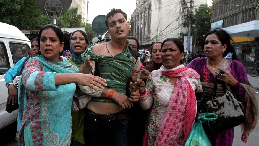 Women activists of Pakistan's Muttahida Qaumi Movement rescue a supporter after a clash with police in Karachi, Pakistan, Monday, Aug. 22, 2016. Pakistani officials say protesters have attacked TV stations and clashed with police in the southern city, leaving one person dead and eight others wounded, including three media workers. (AP Photo/Fareed Khan)