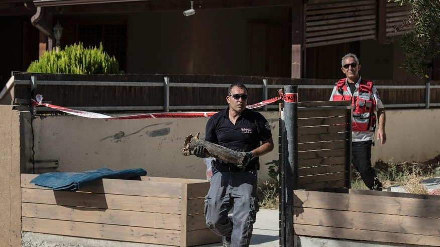 An Israeli police sapper carries part of a rocket which landed in a yard of a house in the city of Sderot, southern Israel, Sunday, Aug. 21, 2016. Palestinian militants in the Gaza Strip fired a rocket into southern Israel on Sunday, prompting the Israeli military to respond with airstrikes and tank fire on targets inside Gaza. No injuries were reported on either side. (AP Photo/Tsafrir Abayov)