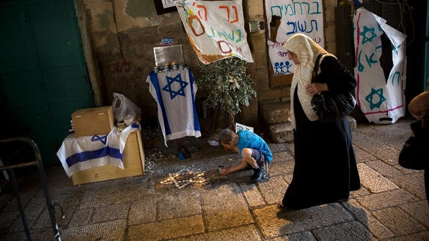 In this Sunday, Oct. 11, 2015 file photo, a Palestinian woman walks by Jewish child as he lights candles where a stabbing attack took place last week in Jerusalem's Old City. A new poll of Israelis and Palestinians released on Monday, Aug. 22, 2016, found that a slim majority on both sides still favor a peace settlement establishing a Palestinian state alongside Israel, despite years of conflict and deadlock in negotiations. The results of the joint poll may provide some small signs of encouragement when peace prospects appear bleak. (AP Photo/Oded Balilty, File)