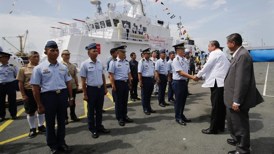 FILE - In this Thursday, Aug. 18, 2016 file photo, Philippine Transportation and Communications Secretary Arthur Tugade, second from right, greets the crew of the Philippines' BRP Tubbataha as it arrives for handover ceremonies at the Philippine Coast Guard headquarters in Manila, Philippines on Thursday, Aug. 18, 2016. The Philippine coast guard took possession last week of the first of nine multi-role response vessels being provided by Japan in an effort to boost a chronic shortage of maritime assets amid Manila's territorial dispute with China in the South China Sea. (AP Photo/Aaron Favila, File)